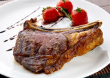 grilled-meat-ribs-white-plate-tomatoes-18712247